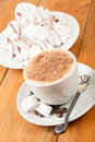 Fresh cappuccino with foam served with sugar cubes and meringues Royalty Free Stock Photography