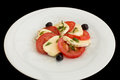 Fresh caprese salad in white plate on a black background Stock Image