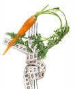 Fresh carrot with leaves on the fork with measuring tape diet concept isolated white background Royalty Free Stock Photo