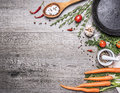 Fresh carrots from the garden with herbs and spices with a vintage cast-iron frying pan wooden rustic background top view borde Royalty Free Stock Photo