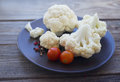 Fresh cauliflower and cherry tomatoes on a brown round plate on a wooden surface Royalty Free Stock Photo