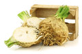 Fresh celery roots with some foliage and a cut one Stock Photography