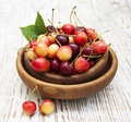 Fresh cherries in bowl on a wooden table Stock Photo