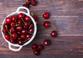Fresh cherries in a bowl on the wooden table Royalty Free Stock Photo