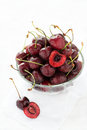 Fresh cherries in glass bowl over light background selective focus Stock Photos