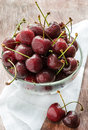 Fresh cherries in glass bowl over wooden background selective focus Royalty Free Stock Image