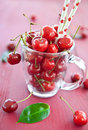 Fresh cherries in a glass mug with paper straws Royalty Free Stock Images