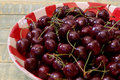 Fresh cherries in red gingham plate sweet on rustic table Royalty Free Stock Images