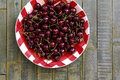 Fresh cherries in red gingham plate sweet and rustic table Stock Photo