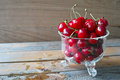 Fresh cherries red in glass bowl against wooden background Royalty Free Stock Photos