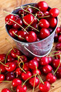Fresh cherries in a small bucket on wooden table surface summer fruits closeup Stock Image