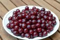 Fresh cherries on white plate and shiny dark red the Stock Image