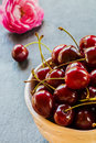Fresh cherries in white vintage bowl on black stone background and pink rose. Selective focus Royalty Free Stock Photo