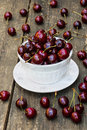 Fresh cherries in white vintage bowl on old wooden table. Ripe berries on background, summer day Royalty Free Stock Photo