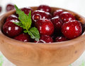 Fresh cherries in a wooden bowl on white table macro photo Stock Photography