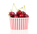 Fresh cherry berries in striped bucket on white background Royalty Free Stock Photo
