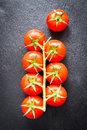 Fresh cherry tomatoes on a black background with spices. Top vie Royalty Free Stock Photo