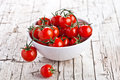 Fresh cherry tomatoes in a bowl on rustic wooden background Stock Photo