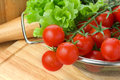 Fresh cherry tomatoes closeup chopping board salad leaves background Royalty Free Stock Images