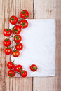 Fresh cherry tomatoes and piece of paper on wooden background Royalty Free Stock Photography