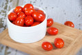 Fresh cherry tomatoes in white bowl on wooden cutting board shallow depth of field Stock Photos