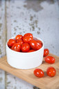 Fresh cherry tomatoes in white bowl on wooden cutting board shallow depth of field copy space Stock Photos
