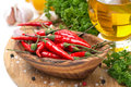 Fresh chili pepper garlic spices and oil on a wooden board close up Stock Photo