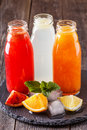 Fresh citrus juices on a dark wooden background. Royalty Free Stock Photo