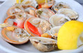 Fresh clams served with lemon Stock Photos