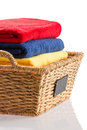 Fresh clean towels in a wicker basket colorful stack of neatly folded red blue and yellow conceptual of cleanliness hygiene and Royalty Free Stock Images