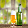 Fresh cold beer in a glass and in a bottle on rustic wooden table with natural background outside the window Royalty Free Stock Photography