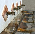 Water pours from ornamental spouts. Royalty Free Stock Photo