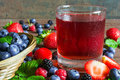 Fresh cold summer berries juice in a glass with ripe berries in Royalty Free Stock Photo