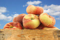 Fresh colorful flat peaches donut peaches in a wooden crate against a blue sky with clouds Stock Photos