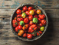 Fresh colorful ripe heirloom tomatoes in basket over wooden background Royalty Free Stock Photo