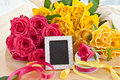 Fresh colorful roses yellow and pink and a little blackboard with copy space Royalty Free Stock Photo