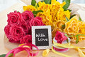 Fresh colorful roses yellow and pink and a little blackboard with copy space Royalty Free Stock Image
