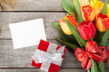 Fresh colorful tulips with gift box and greeting card
