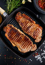 Fresh cooked meat Beef Steak Sirloin for two. in iron grilled pan with herbs. Royalty Free Stock Photo