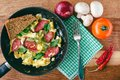 Fresh cooked scrambled eggs in pan with sausage and herbs. Bread, fork, vegetables, napkin on wooden board, top view. Royalty Free Stock Photo