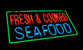 Fresh and cooked seafood old neon light store sign dusty vintage fluorescent at a fish market Royalty Free Stock Images