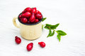 Fresh cornel berries in an iron mug on a white table. Red seasonal berries. Royalty Free Stock Photo