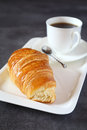 Fresh croissants and cup of coffee on dark background Royalty Free Stock Photo