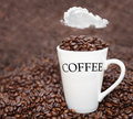 Fresh cup of coffee beans with white fluffy cloud above Royalty Free Stock Photos