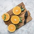 Fresh cut oranges with leaves and a wooden crush for fruit, on rustic wooden tray, top view Royalty Free Stock Photo