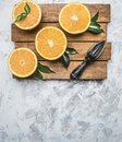 Fresh cut oranges with leaves and a wooden crush for fruit, on rustic wooden tray, top view, space for text Royalty Free Stock Photo