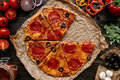 Fresh delicious pizza with pizza ingredients on the wooden table, top view Royalty Free Stock Photo