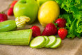Fresh detailed fruit - strawberries, courgettes, lemon, apple and green salad Royalty Free Stock Photo