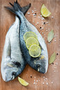 Fresh dorada fish with sea salt lime and bay leaf over wooden background Royalty Free Stock Images