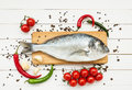 Fresh dorado fish on wooden cutting board with vegetables on white wooden table. Top view